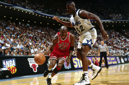 Michael Jordan drives past Shaquille O'Neal
